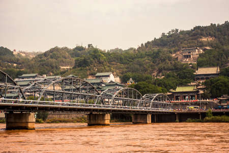 Lanzhou, China - 20 June, 2009: Zhongshan Bridge crossing a dirty and pollued river in the center of Lanzhou, Gansu Province
