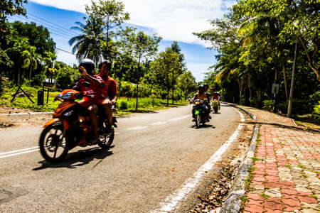 Kota Kinabalu, Malaysia - 20 November, 2009: Local people riding motorbikes along a road in the jungle next to Kota Kinabalu city