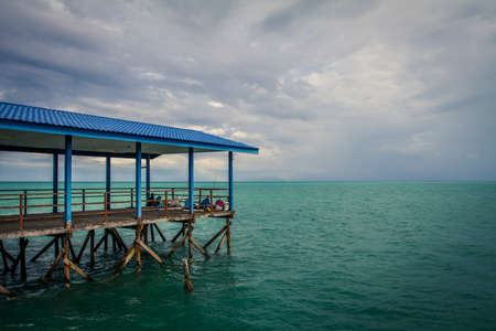 Jetty leading to the South China Sea with locals fishing