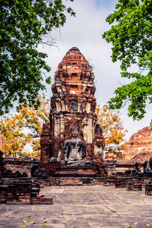 Ancient ruins with carved stone buddhas and temples at the Ayutthaya Historial Park in Thailand Stock Photo