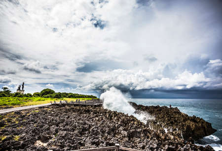 Bali, Indonesia - 10 April, 2013: Waves crashing into the volcanic shoreline at a location named Water Blow on the Nusa Dua Peninsula.
