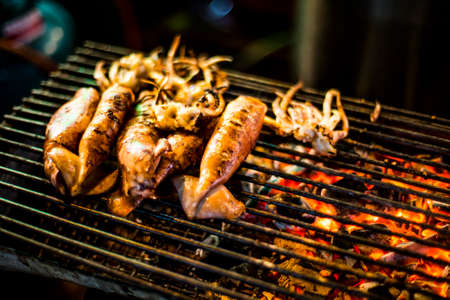 Grilled squid as street food in Bangkok Chinatown district Stock Photo