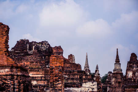 Ancient ruins with carved stone buddhas and temples at the Ayutthaya Historical Park in Thailand