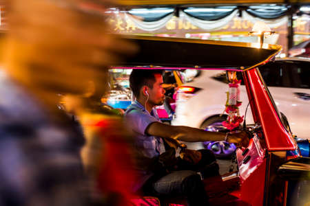 Bangkok, Thailand - 25 February, 2017: People, Motorbikes and Tuk-Tuks crowded on the lively Yarowat Road, also known as Chinatown, in the late evening. The district is world renowned for street food Editorial