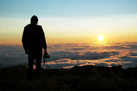 Silhouette of the photographer which looks at a dawn in mountains