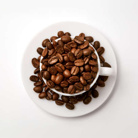White cup filled with coffe beans