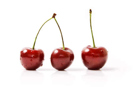 Three Cherries with dewdrops on white background Stock Photo
