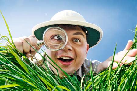 Jeune homme est surpris à ce qu'il trouve dans l'herbe quand regarde à travers un verre grossissant