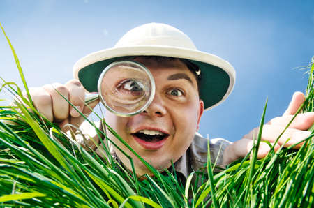 explorer man: Young Man is Surprised at What He Finds in Grass when Looks through a Magnifying Glass