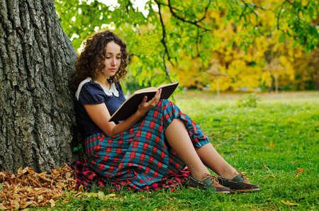 The girl with book sitting under the tree
