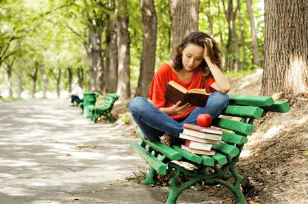 The girl sitting on a bench, reading a book
