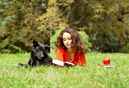 The girl and dog lying on a grass in park Stock Photo