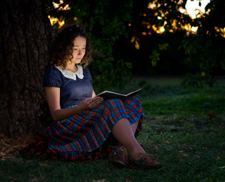 The girl with book sitting under the tree, twilight  The book is open and emitting a wonderful glow of light  Stock Photo