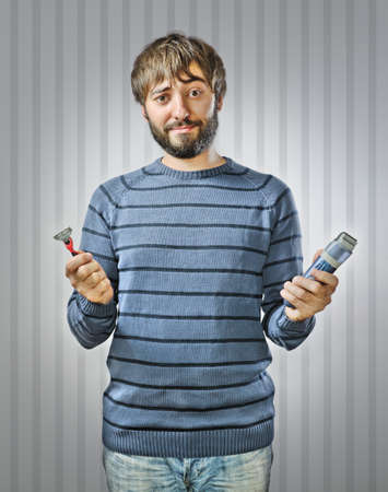Unshaved Young Man Choosing between Razor and Hair Clipper photo