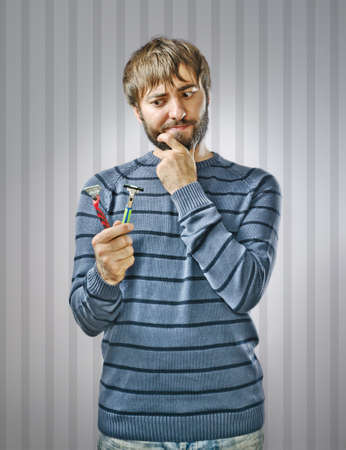 Unshaved Young Man Choosing between Two Razors Stock Photo - 15726029