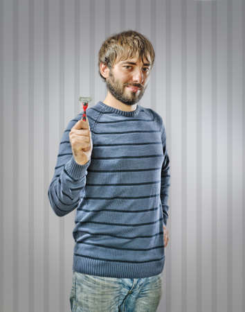 Unshaved Young Man holding a Razor Stock Photo - 15726028