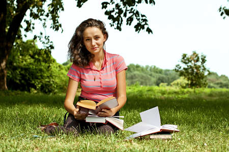 The girl sitting on a grass, reading a book Stock Photo