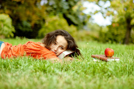 The girl with books lying on a grass Stock Photo
