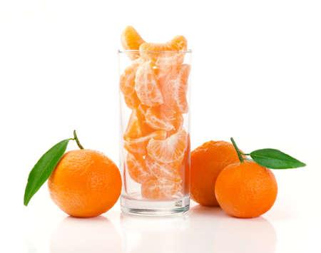 Mandarina fresca y segmentos en un vidrio aislado en blanco Foto de archivo