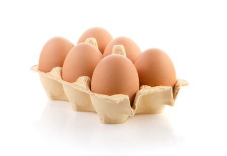 Six brown eggs in carton on white