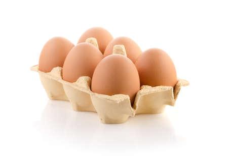 Zes bruine eieren in de doos op wit
