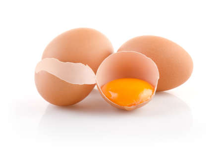 Brown Eggs with one broken on white background