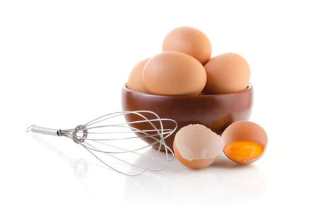 stainless background: Brown Eggs in a bowl with whisk on white background