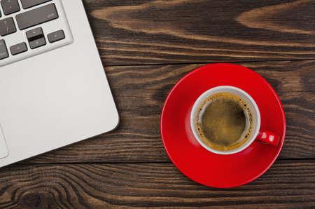 trabajando en casa: Ordenador y la taza de caf� sobre fondo de madera vieja Foto de archivo