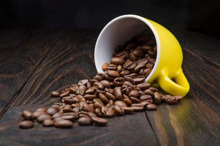 frijol: Granos de caf� en una taza en el fondo de madera vieja