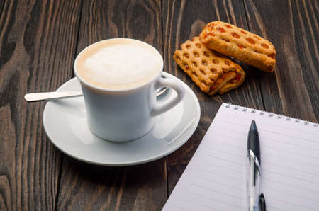 Cup Coffee and Note Pad on old wood background