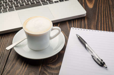 Cup Coffee, Computer and Note Pad on old wood background