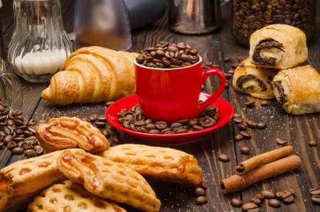 processed grains: Cup of Coffee Beans with Pastry on brown wood table background Stock Photo
