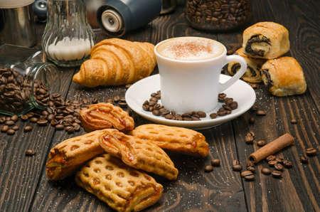 capuchino: Taza de café con pasta en el fondo de la tabla de madera marrón
