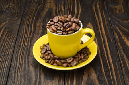 Coffee Beans in a Cup on old wood background Archivio Fotografico