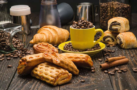 Cup of Coffee Beans with Pastry on brown wood table background Stock Photo