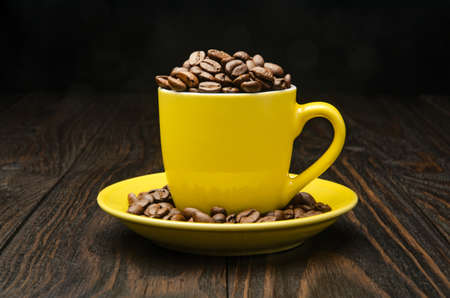 Coffee Beans in a Cup on old wood background Stock Photo
