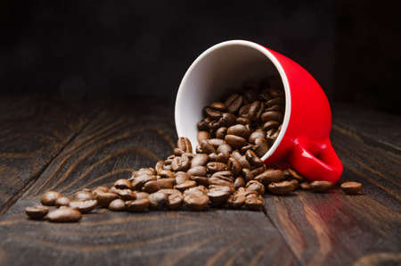 processed grains: Coffee Beans in a Cup on old wood background Stock Photo