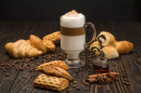 Cup of Coffee with Pastry on brown wood table Stock Photo