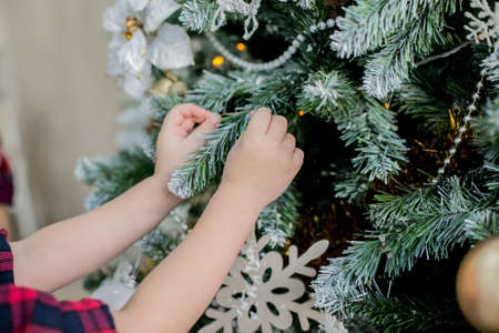 decorate: child decorate a Christmas tree