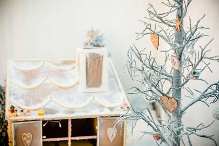 Gingerbread house in christmas landscape surrounded by candy canes and sweets photo