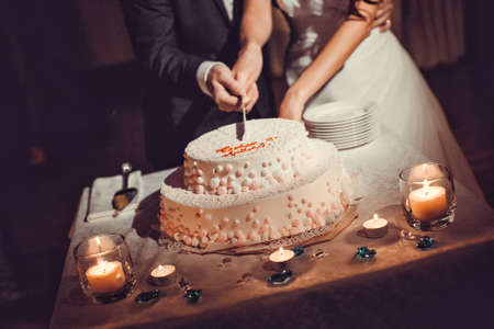 A bride and a groom is cutting their wedding cake Imagens