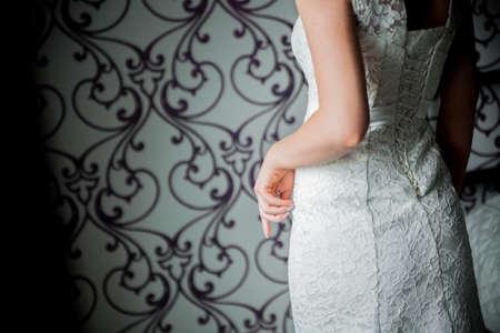 zip tie: Bride putting on her white wedding dress
