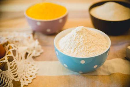 indispensable: flour, eggs, foam egg whites, egg beater, rolling pin and egg shells on wooden table