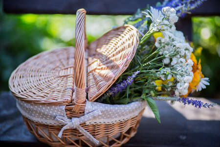 basket of flowers standing on a wooden background Stock Photo
