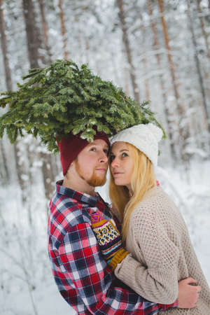 young couple in a plaid shirt with fir twigs walk in the winter woods