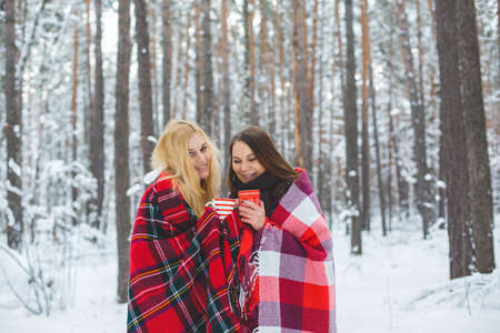 red plaid: two girls sheltered red plaid hold mugs a drink in a snowy forest Stock Photo