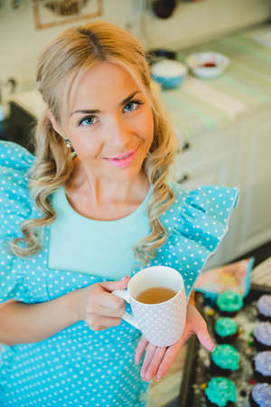 young blond woman drinking tea in the kitchen
