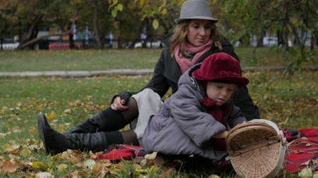 Mom and daughters play in the park, lie on a rug, throw leaves Stock Photo