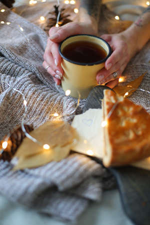 Christmas composition. female hands holding a mug on a sweater.Flat la Imagens