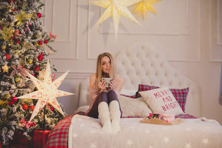 young woman in christmas interior. Sit with a plaid and a cup of tea. Stock Photo